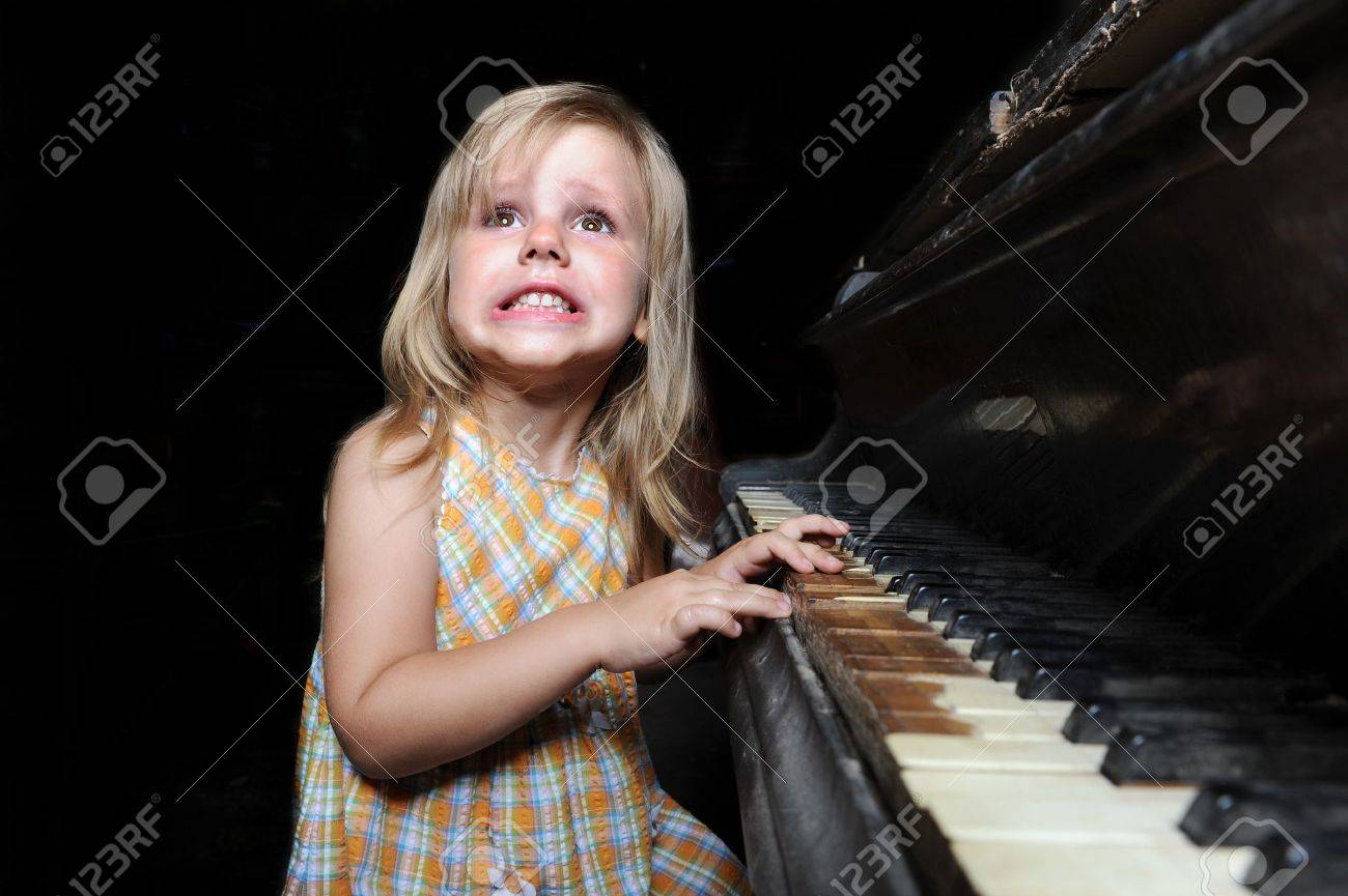 Funny girl playing on an old black piano Stock Photo - 8404282