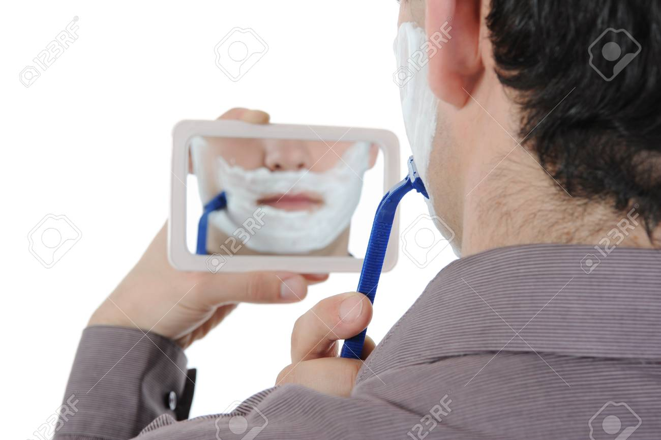 Young man shaving at the mirror. Isolated on white background Stock Photo - 8442185