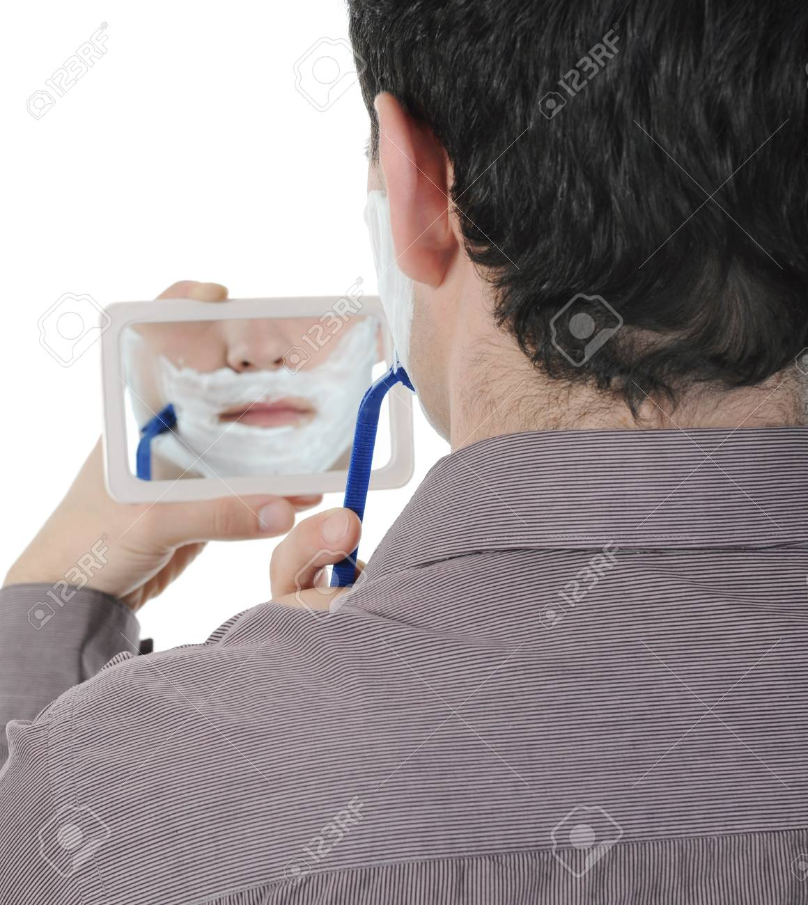 Young man shaving at the mirror. Isolated on white background Stock Photo - 8596829