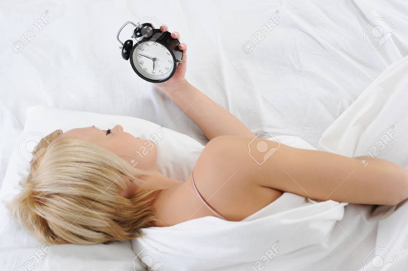 Sleepy woman turns off the alarm Stock Photo - 8735316