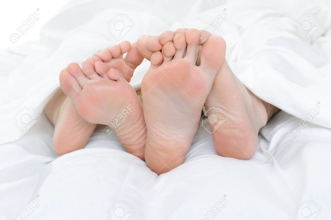 Close-up of the feet of a couple on the bed Stock Photo - 8955349