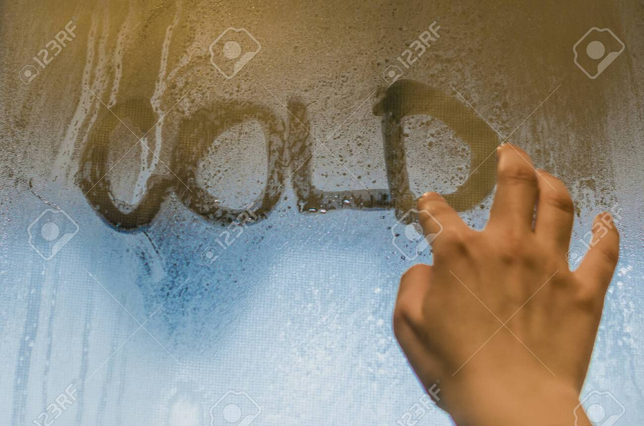 Human Hand Writing Word 'Cold' On The Foggy Window. Water Droplets  Condensation Background Of Dew On Glass, Humidity And Foggy Close Up View.  Outside The House, Bad Raining Weather. Stock Photo, Picture