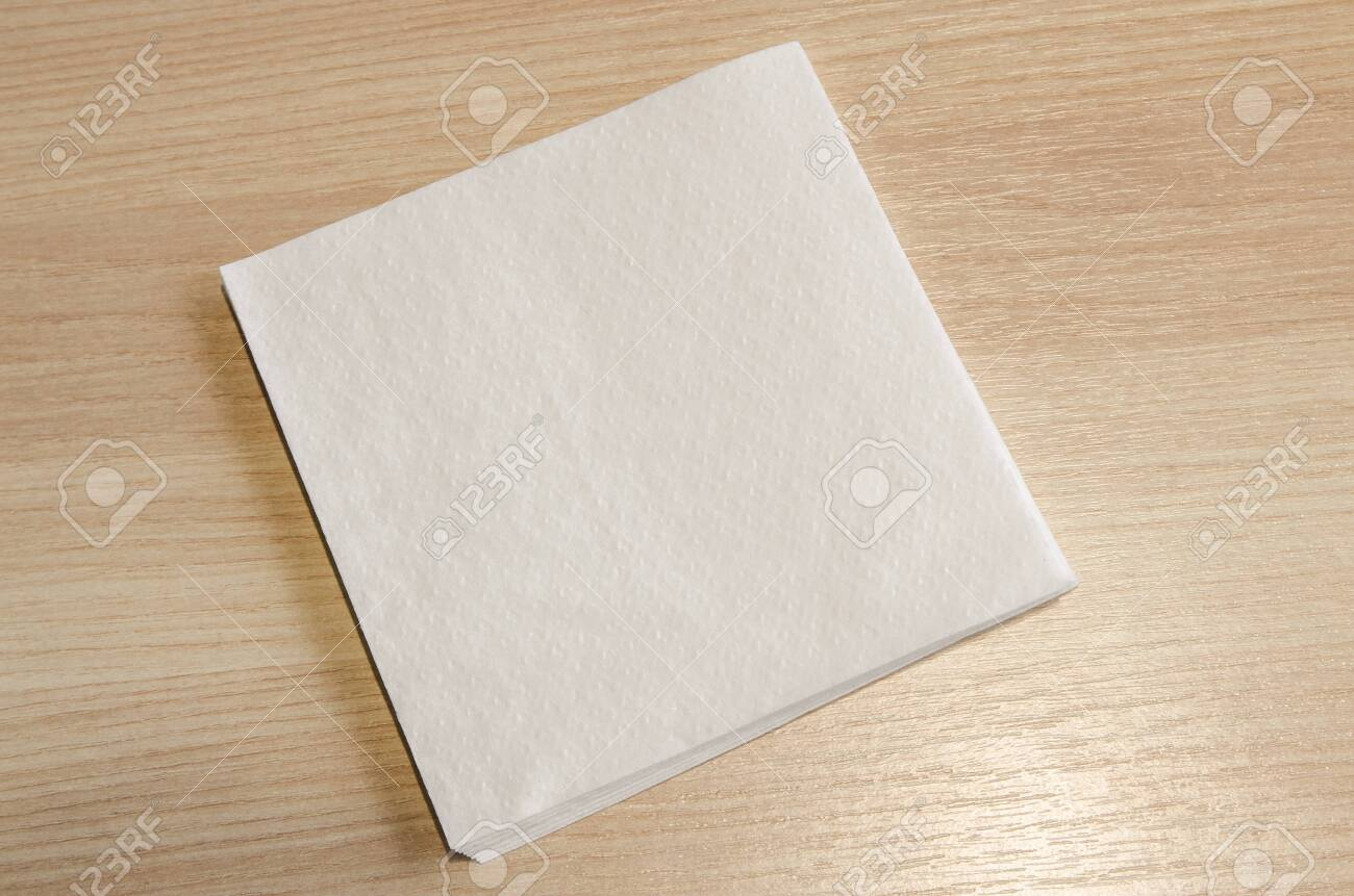 A white napkin on a wooden table background. Stay clean while eating concept. - 123252317