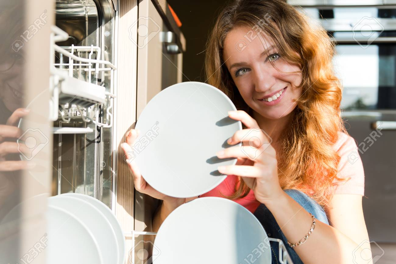 Housework: young woman putting dishes in the dishwasher Stock Photo - 22557017