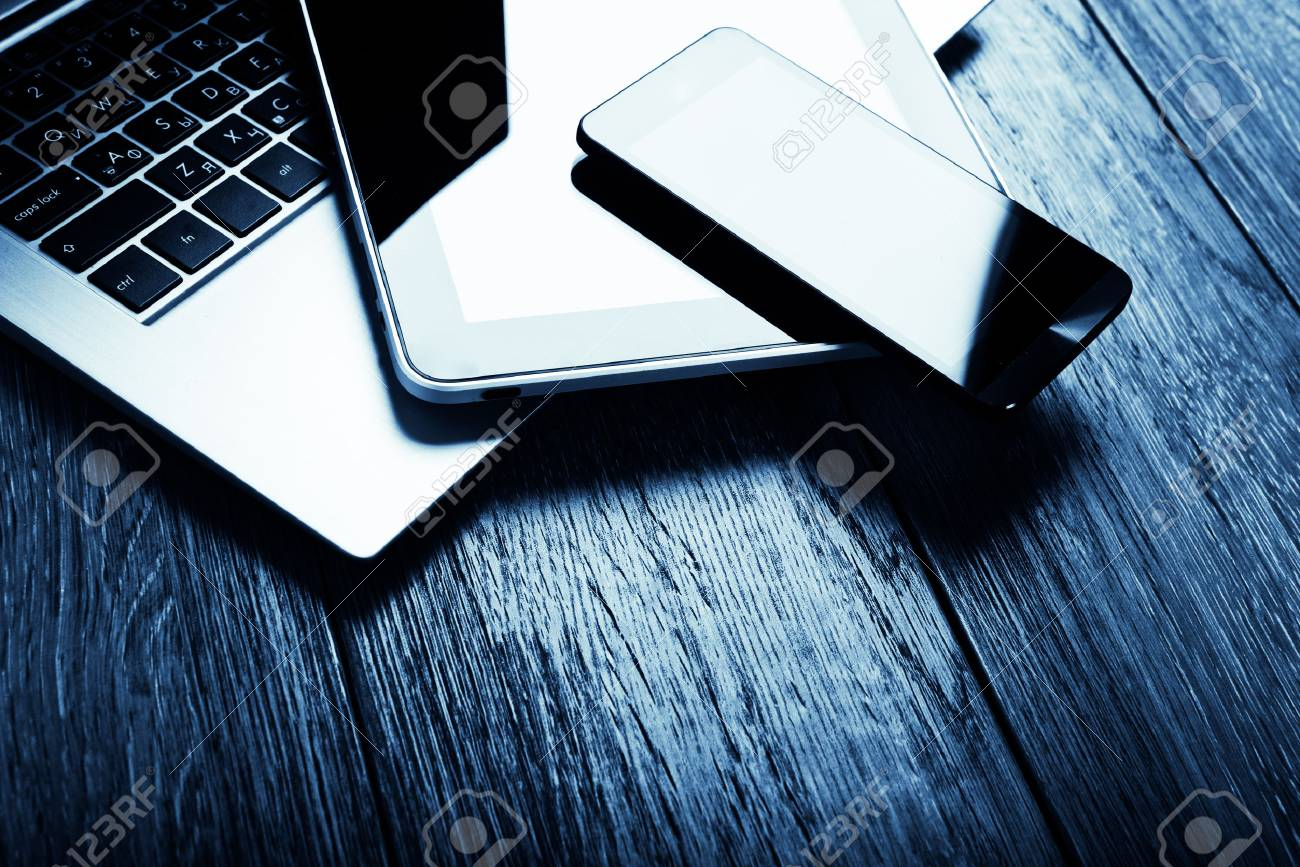 keyboard with phone and tablet pc on wooden desk. Blue toned - 40842562
