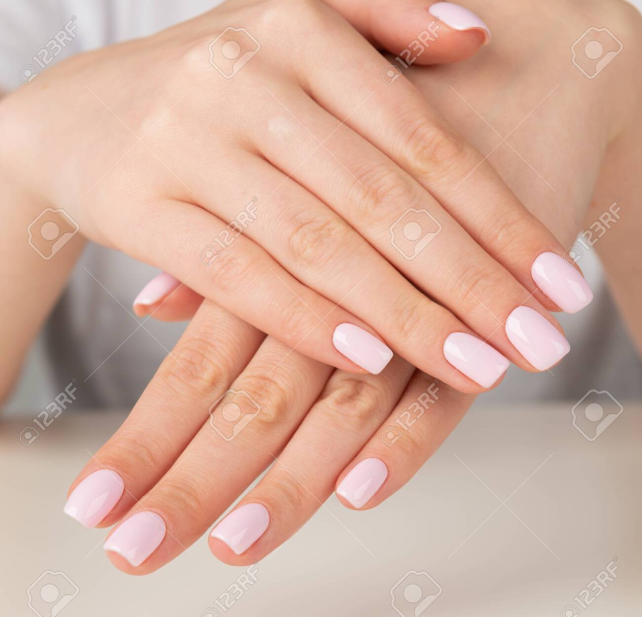 Beautiful female hand with light pink nail design. - 130952196