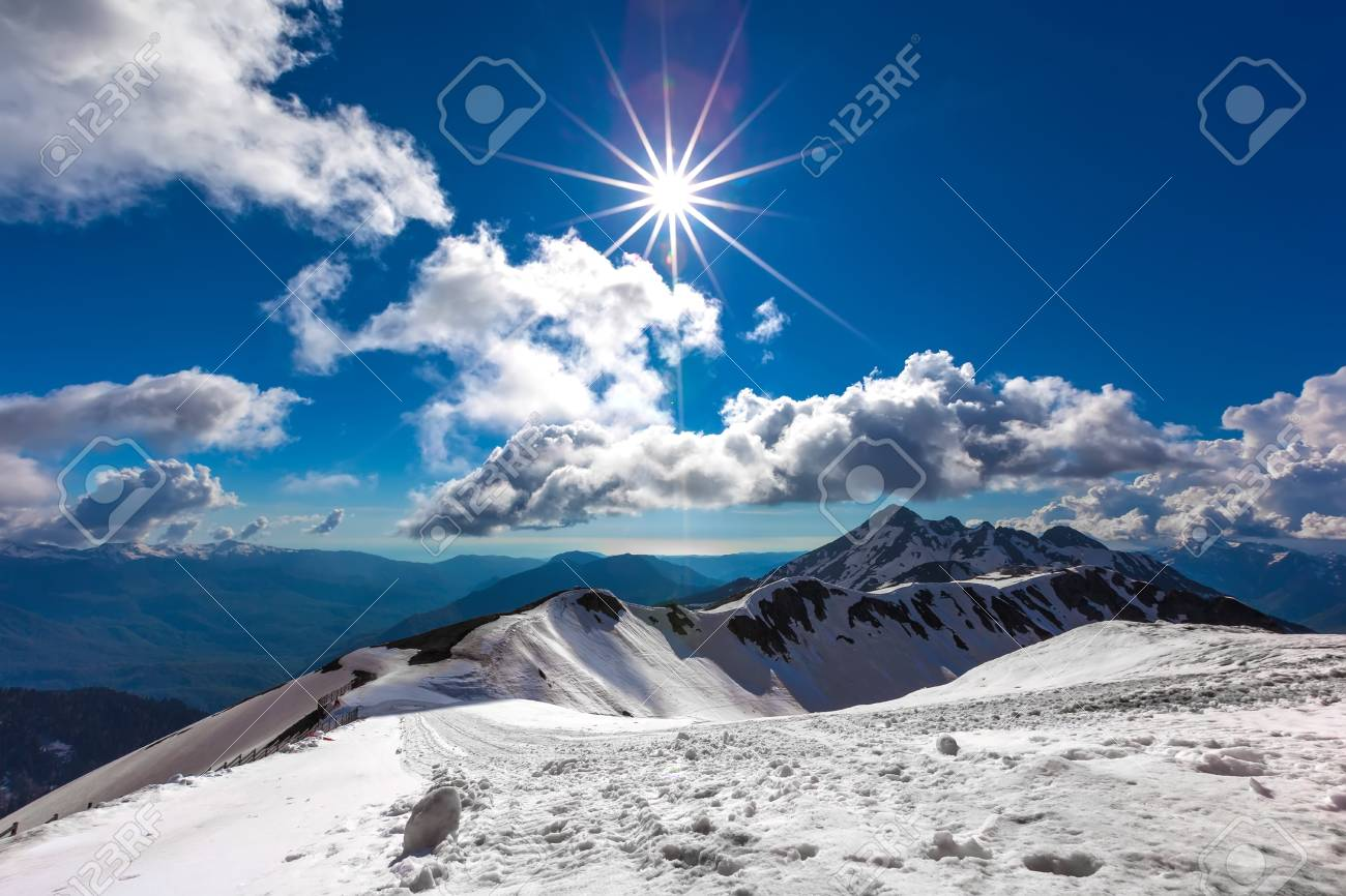 snow covered ski slope at the top in clear weather under a bright