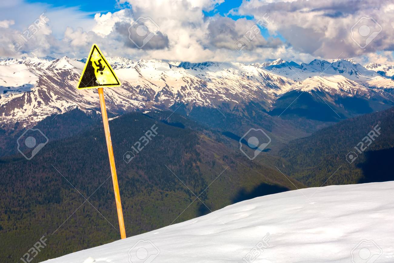 a sign of a steep cliff in a snow-covered glade against a background