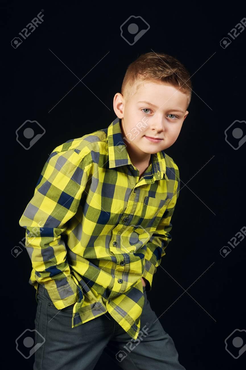 Beautiful gay boy on a dark background .Little model posing in the Studio  Stock Photo