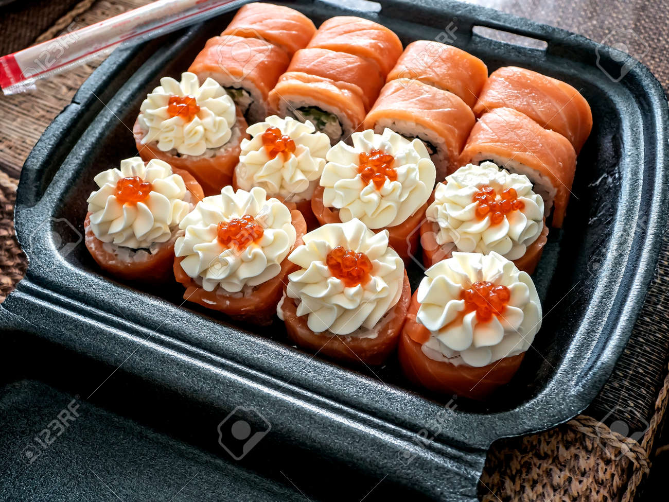 bright little set of sushi rolls in a plastic box - 166725171