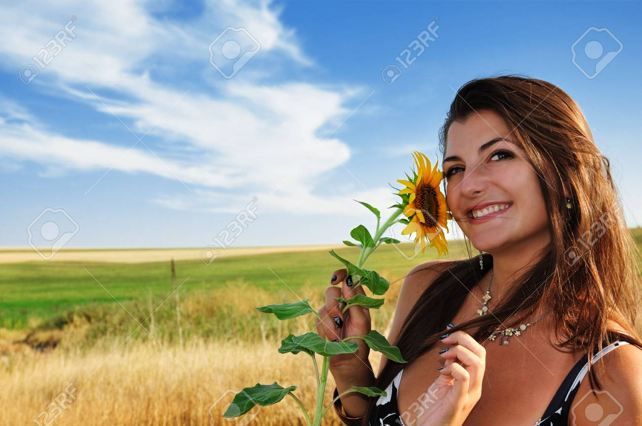 Beautiful girl in a field, holding small sunflower Stock Photo - 5352438