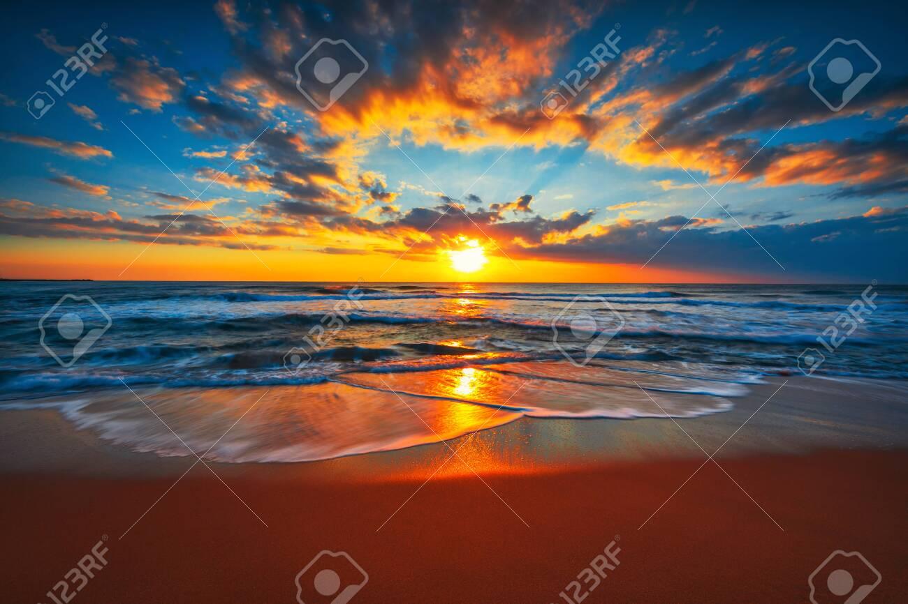 Sunrise on the beach and ocean waves on a tropical sea - 146166430