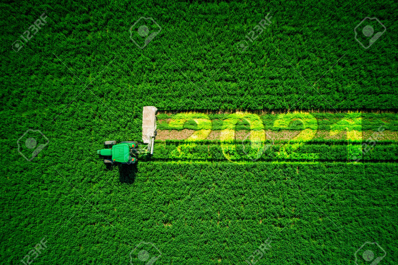 2021 Happy Ney Wear concept and red tractor mowing green field. - 160778596