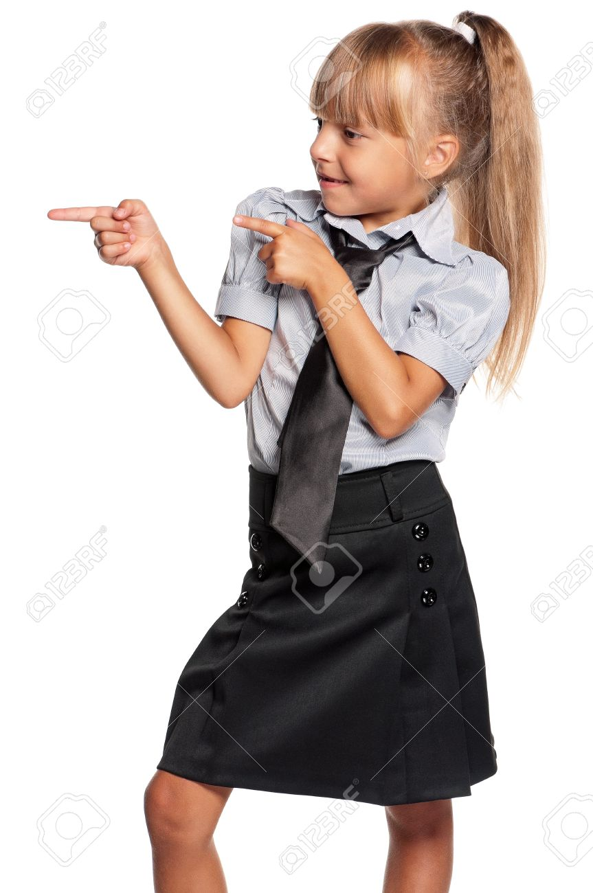 Happy little girl in school uniform showing something isolated on white background Stock Photo - 16380661