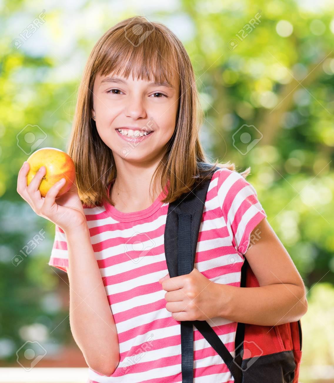 Foto de archivo - Retrato al aire libre de la muchacha feliz 10-11 años de  edad con manzana y mochila. Volver al concepto de escuela.