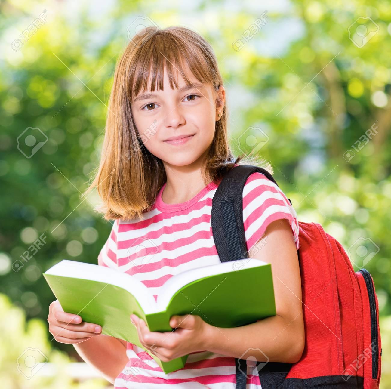 Outdoor Portrait D Une Jeune Fille Heureuse 10 11 Ans Avec Un Livre Sac A Dos De Lecture Retour Au Concept De L Ecole