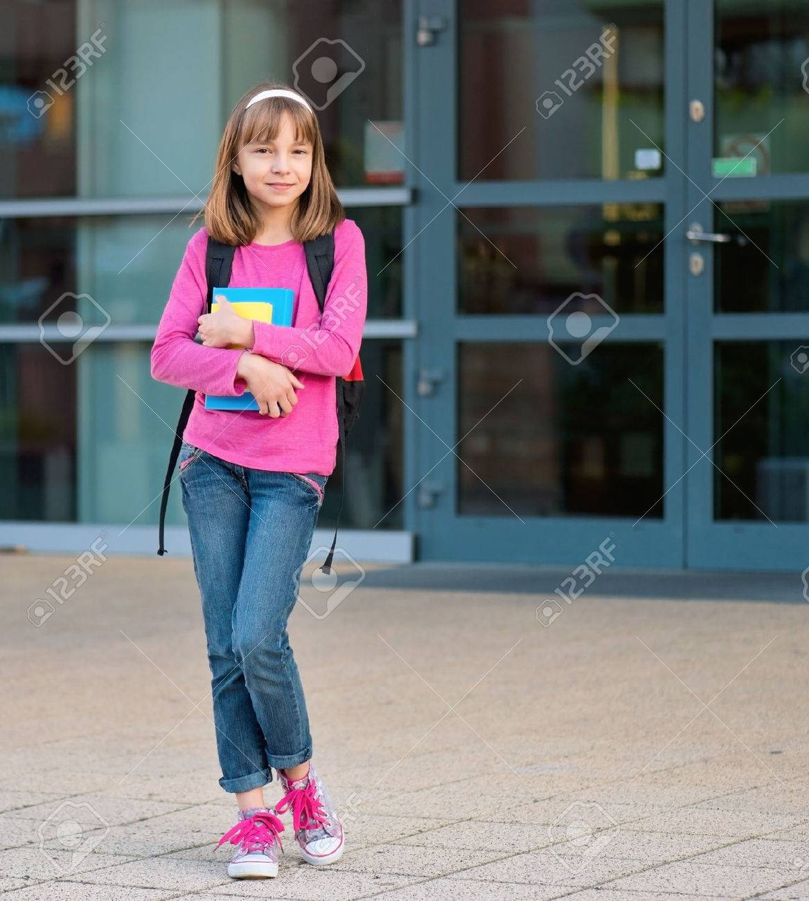 Girl With Book And Backpack Child In Yard On The First School
