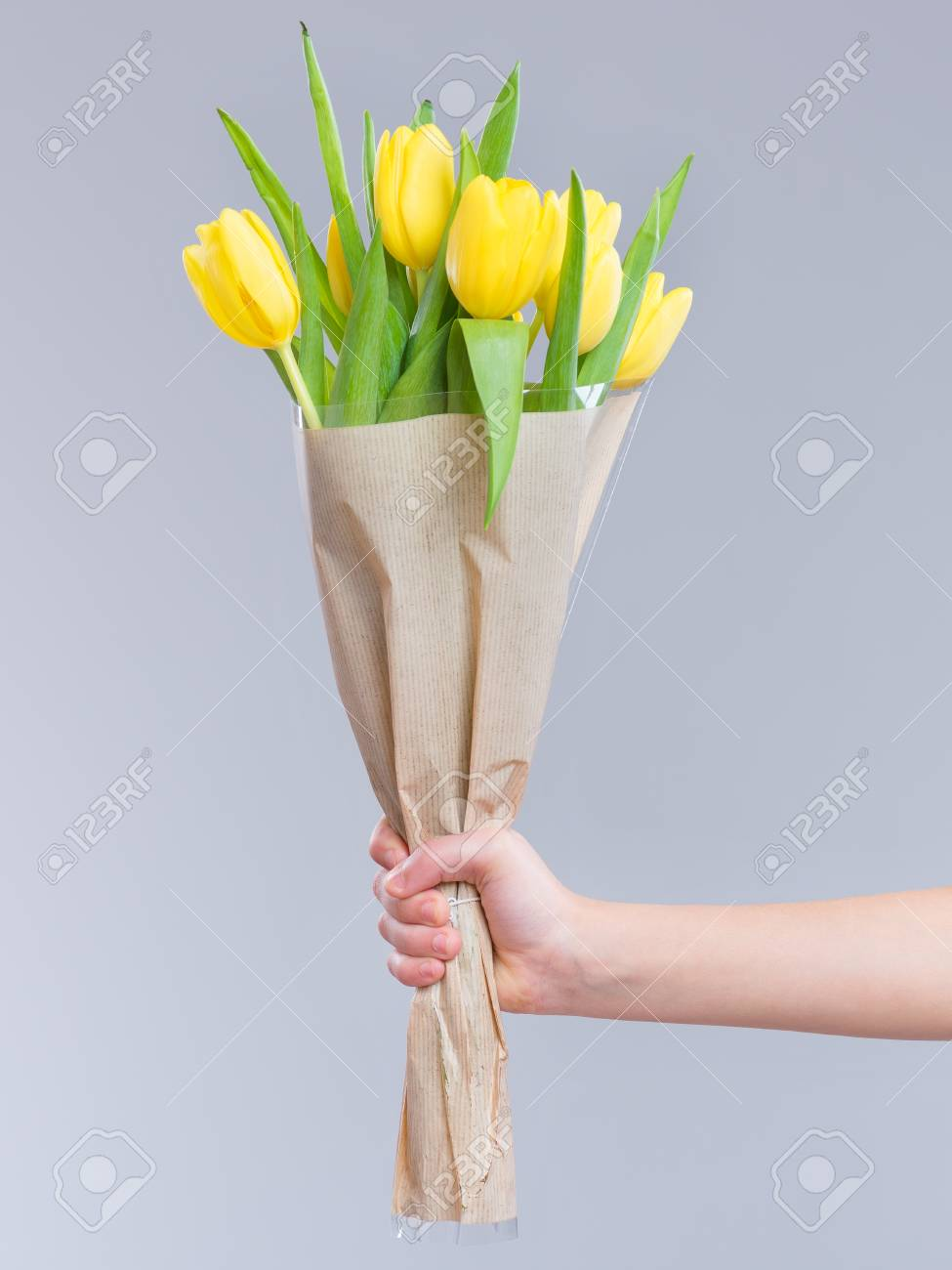 Children Hand Holding Flowers Over Gray Background Bouquet Of