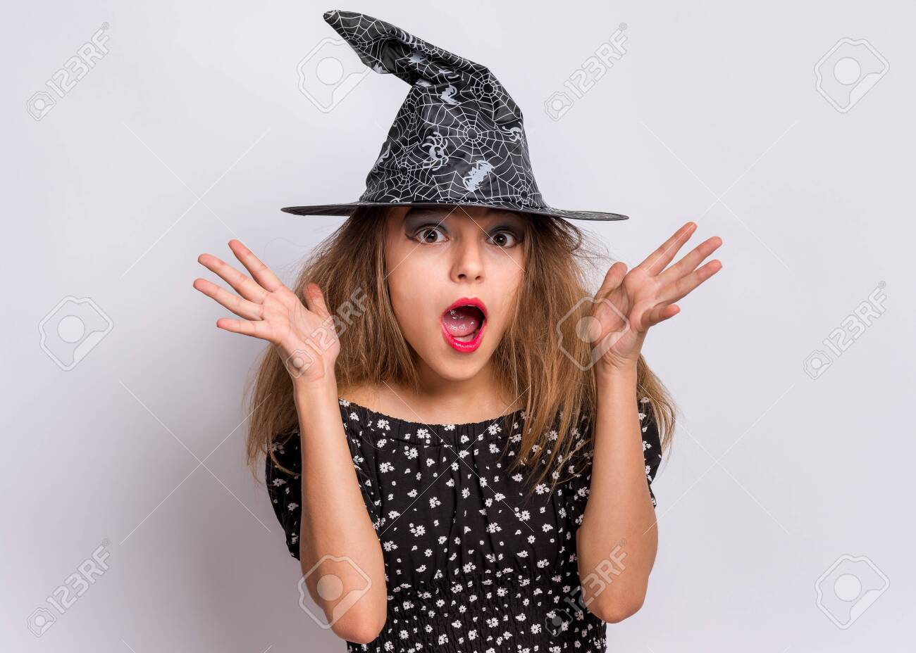 Happy halloween concept. Surprised Teen girl in witch black hat looking at camera in amazement on grey background. Cute child in witch halloween costume shouting, opening eyes and mouth with shock. - 129352606