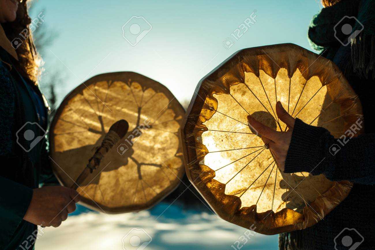 Women holding and playing their sacred drums outdoors in the wintertime - 116780358