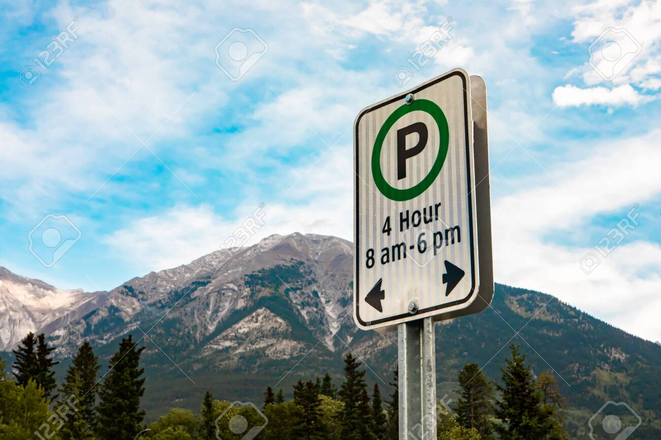 white sign with a green circle, 4 hours parking on specific times 8 am - 6 pm sign, against mountains and the blue sky, British Columbia, Canada - 136810407