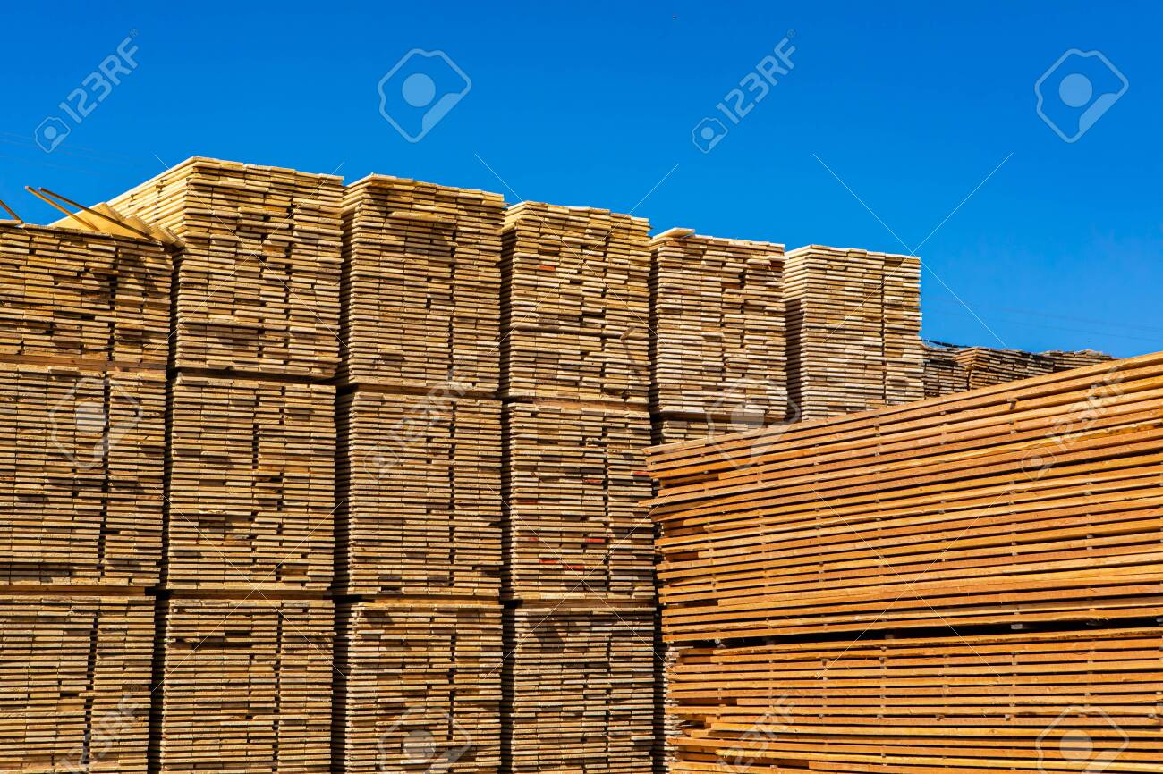 Large piles of sawn and processed wood boards are seen in a sawmill yard. Heavy industry in the Kootenays of British Columbia, Canada. With copy space - 137039607