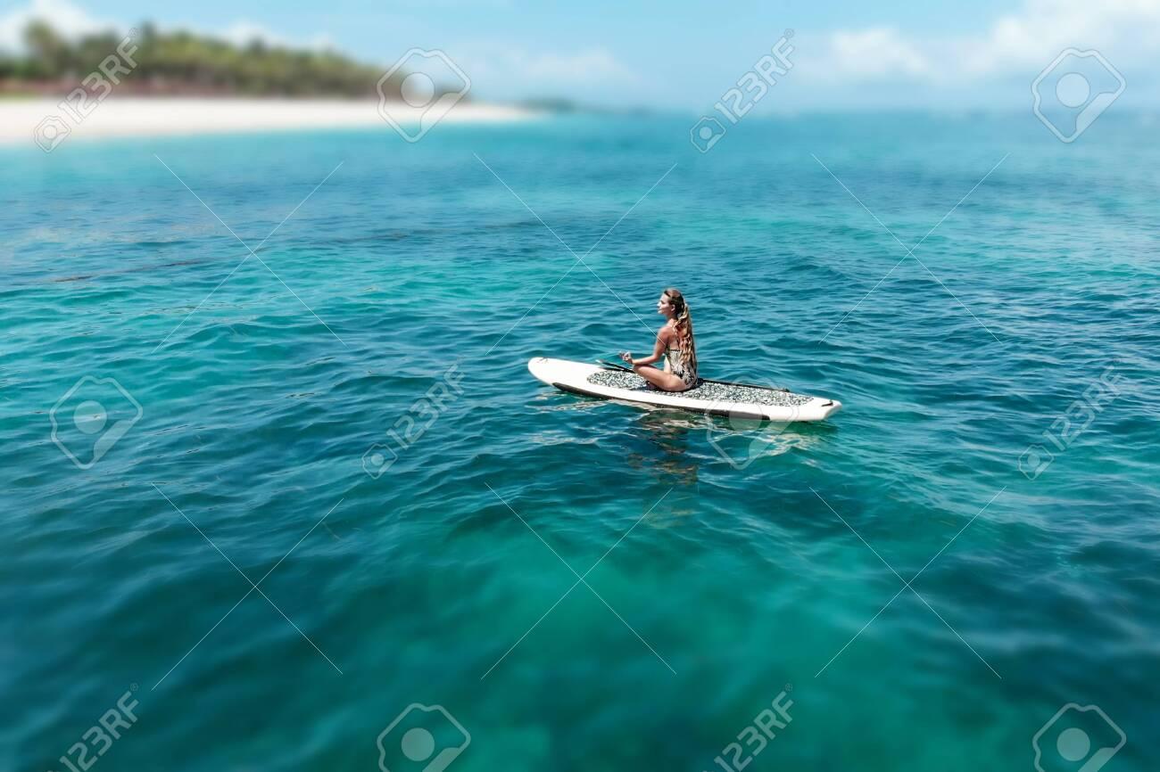 Young Beautiful Woman Meditating In A Sea At Sup Paddleboarding