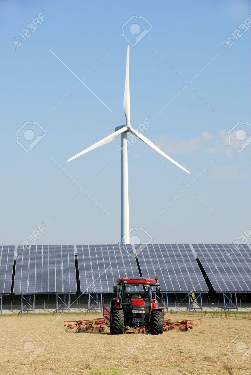 Solar plant with wind turbine at a farm in the Netherlands.In front two tractors - 5358218