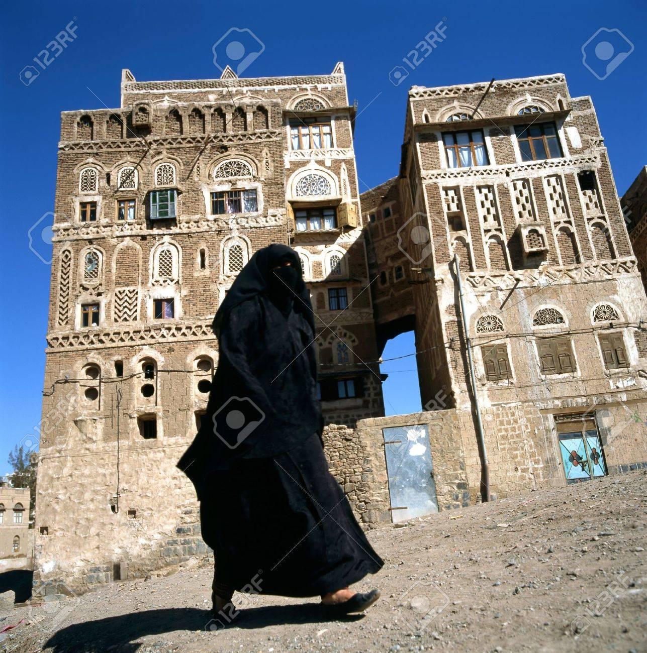 A veiled Muslim woman walks on a Sanaa street, Yemen.At background typical Yemen houses. - 6198594