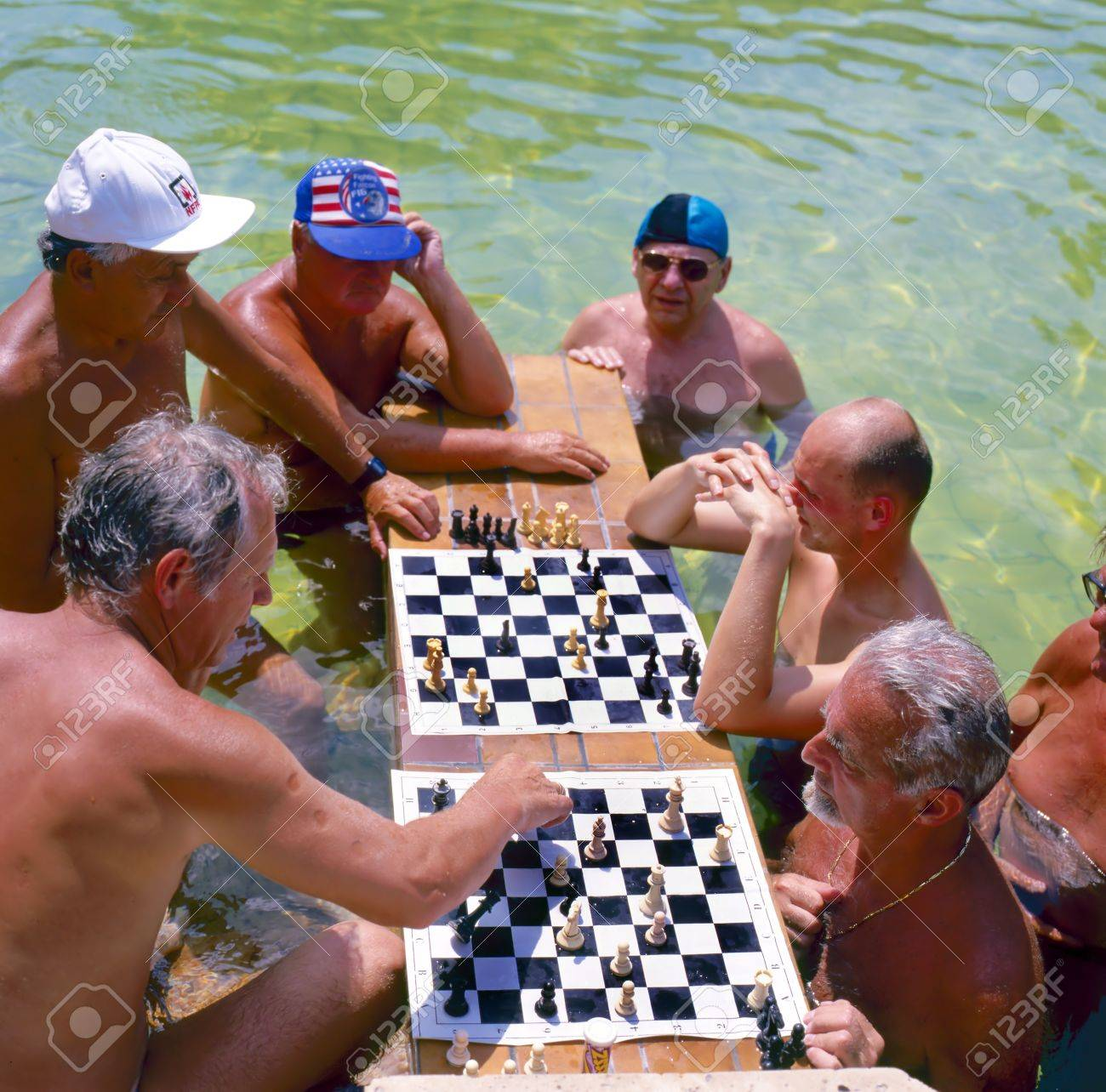 Men playing chess in the Szechenyi thermal baths, spa and swimming pool in Budapest Hungary Focused at the first chess board Stock Photo - 10592756