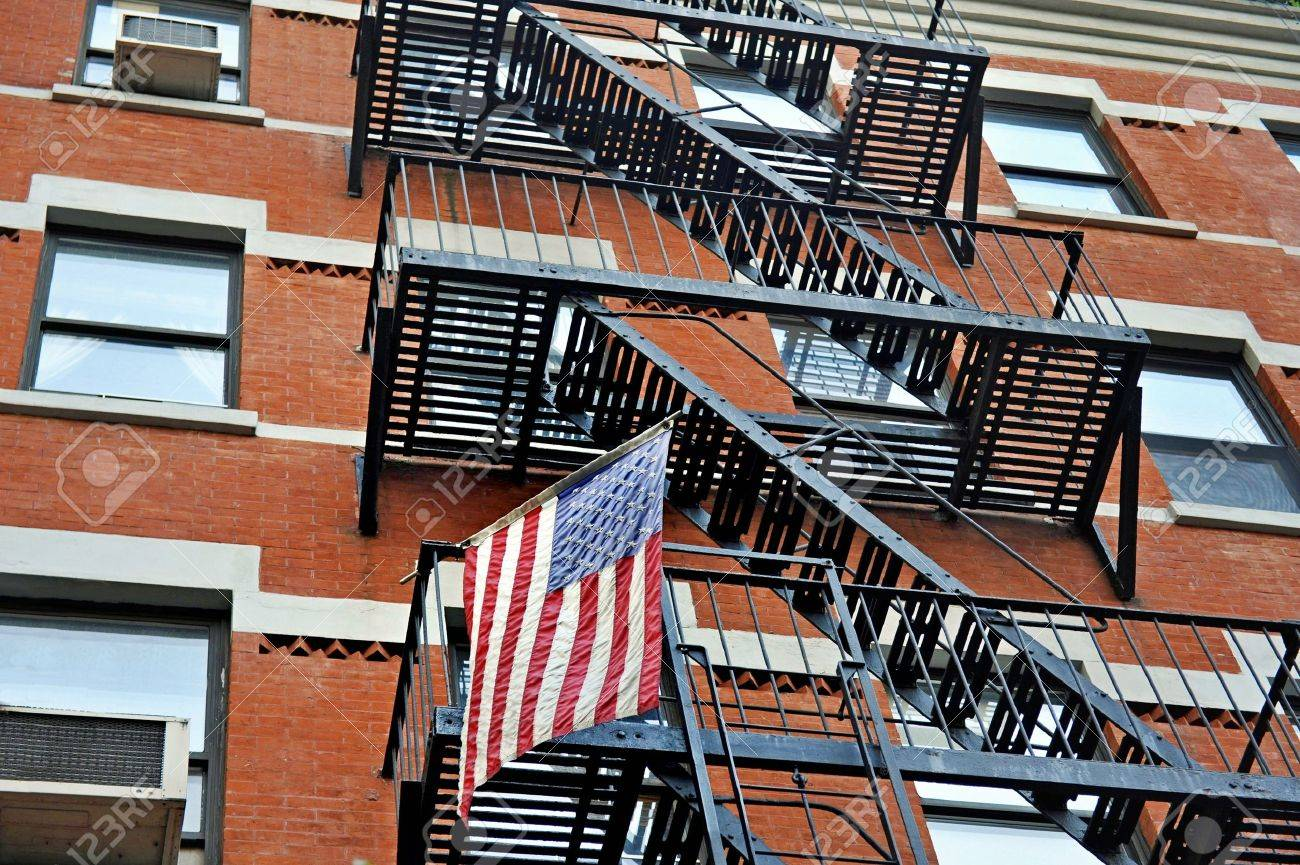 Fire Escape Stairs Outside A New York Apartment Building With The American  National Flag Stock Photo