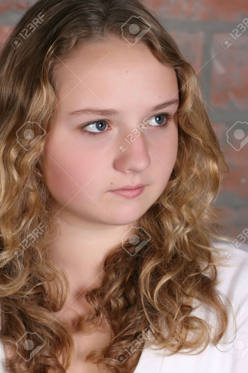 Beautiful teen with curly hair against a brick wall background - 7424723-Beautiful-teen-with-curly-hair-against-a-brick-wall-background--Stock-Photo