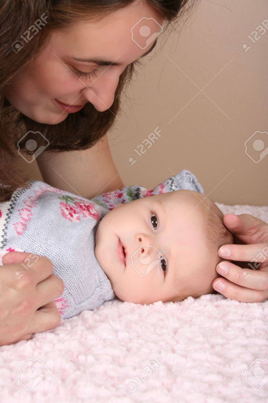 Beautiful brunette mother looking at her two month old baby girl Stock Photo - 8240568