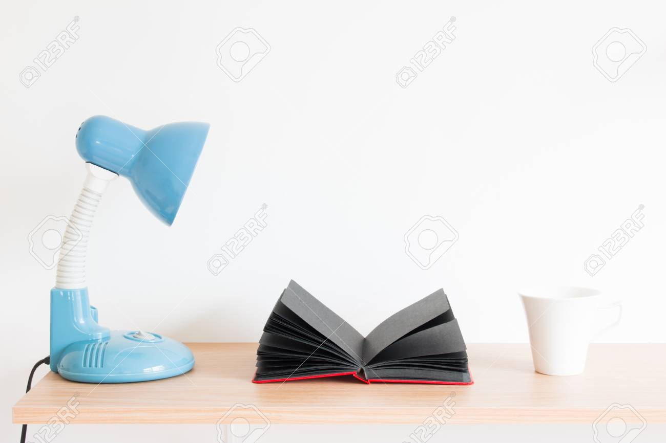 Lampe de bureau bleue carnet noir blanc et tasse à café blanche