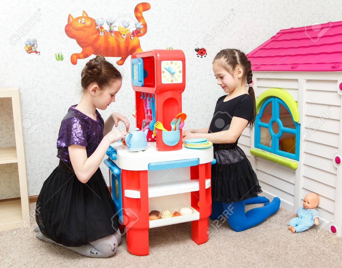 Two Little Girls Play Role Game With Toy Kitchen In Day Care Center Stock  Photo