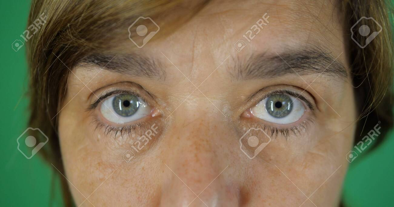 4K - Angry look, frown brows of an adult woman, gray-blue eyes,