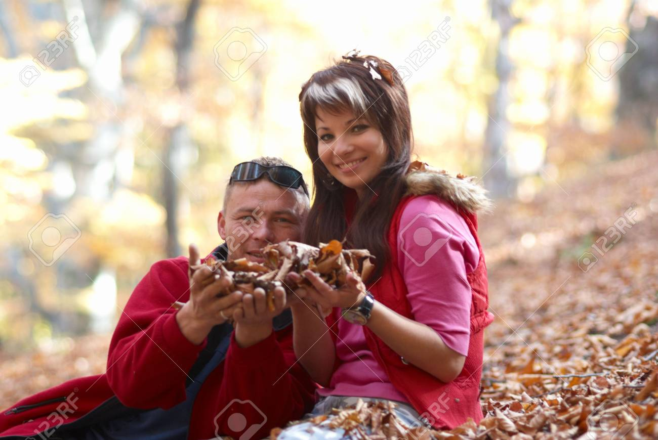 Young couple enjoying the falling leaves in the autumn park Stock Photo - 6068786