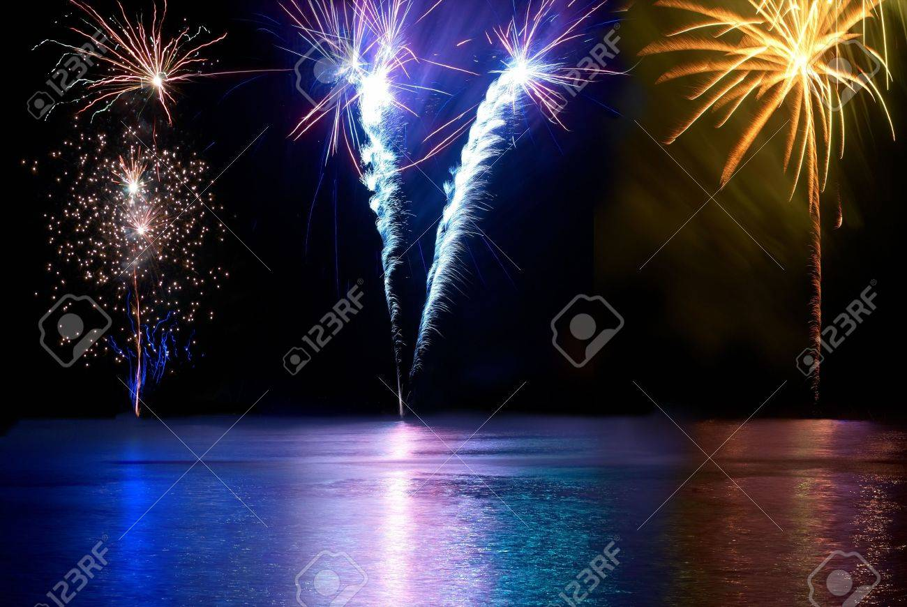 Blue, red, white and yellow colorful fireworks above the river. Holiday celebration. Stock Photo - 11154146