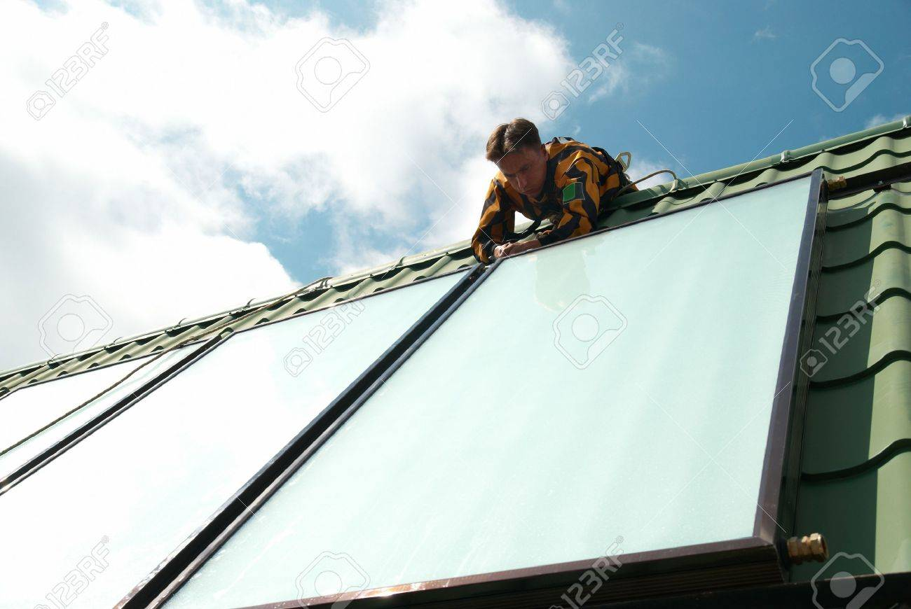 Erector of solar water heating system on the roof. Stock Photo - 12764773