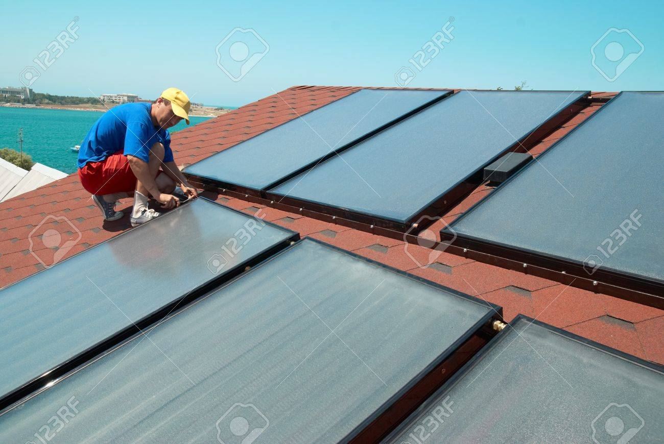 Worker solar water heating panels on the roof. Stock Photo - 15045198