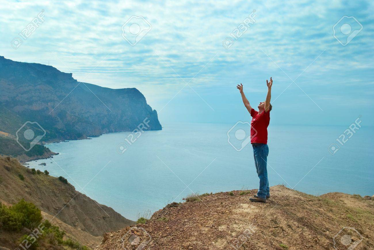 Happy man standing on the cliff with hands up looking at the sea Stock Photo - 15045194