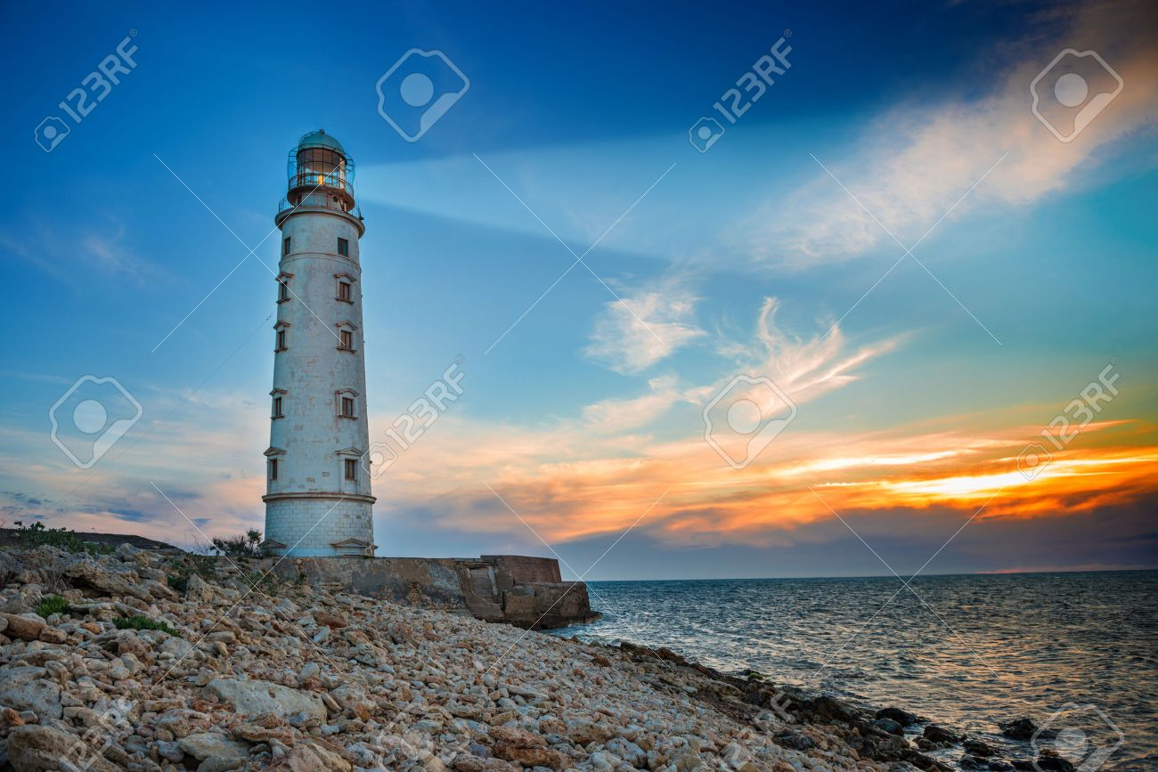 Lighthouse searchlight beam through sea air at night. Seascape at sunset - 39704848