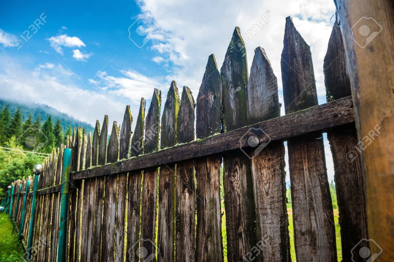 Old Country Fence With Forest And Blue Sky On Background Stock Photo