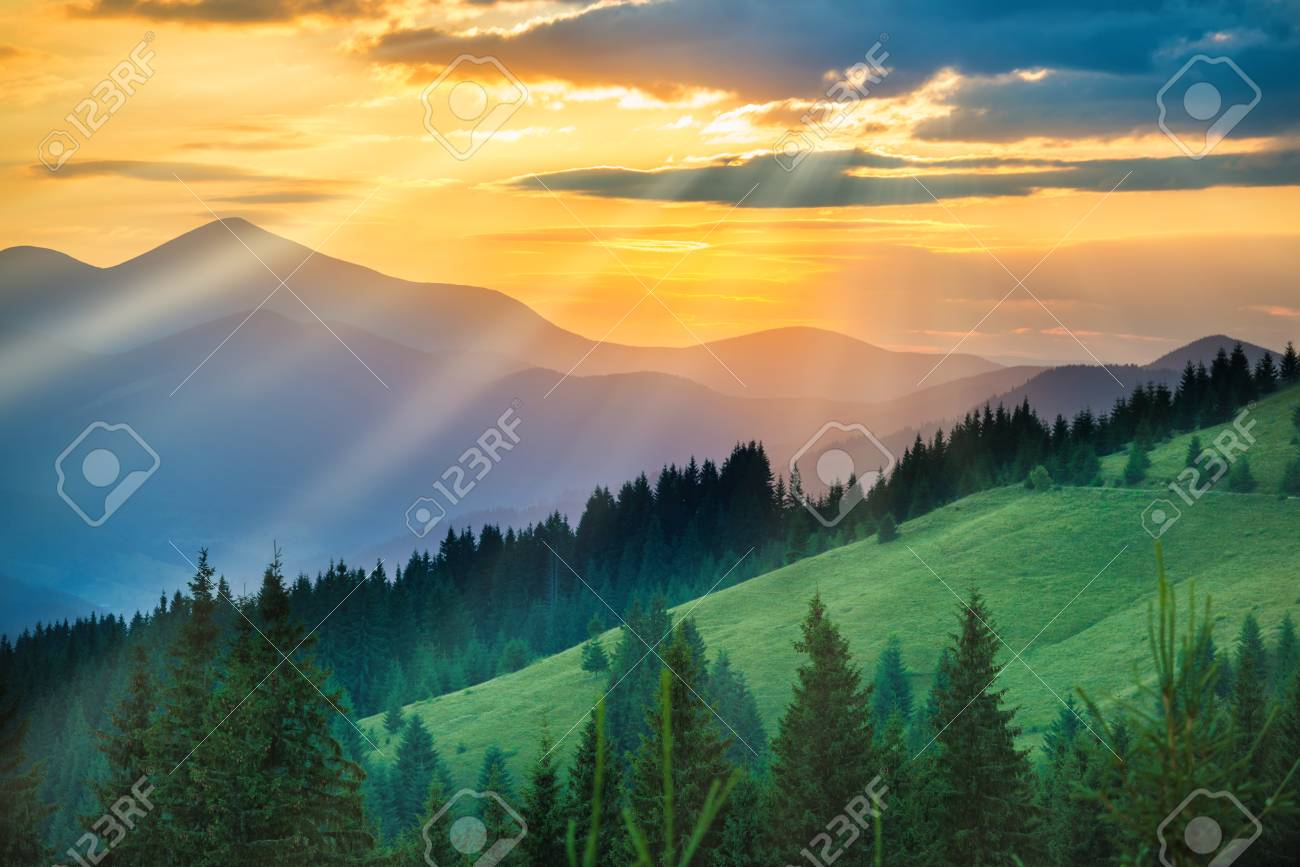 Beautiful Dramatic Sunset In The Mountains Landscape With Sun Shining Through Orange Clouds Stock Photo