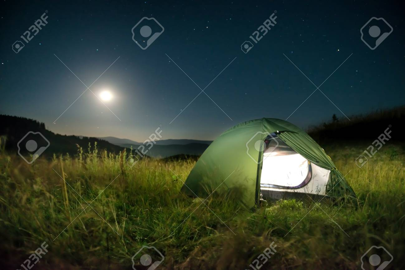Illuminated green tent in the mountains at night under dark sky