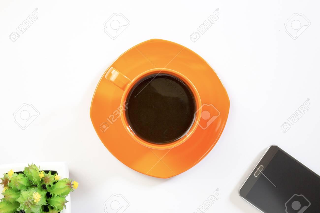 Immagini Stock Caffè Nero In Tazza Arancio Un Telefono Cellulare