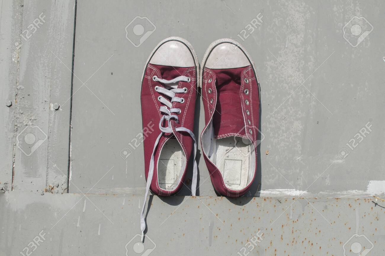 Pair of worn out vintage red old canvas sneakers on grey painted tin surface background - 126450572