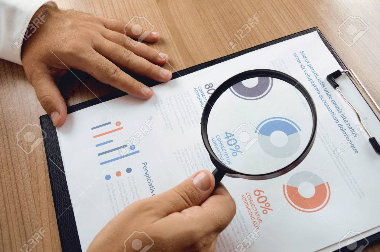 Market Research Businessman Hand Holding Magnifier And Closer Study Report From