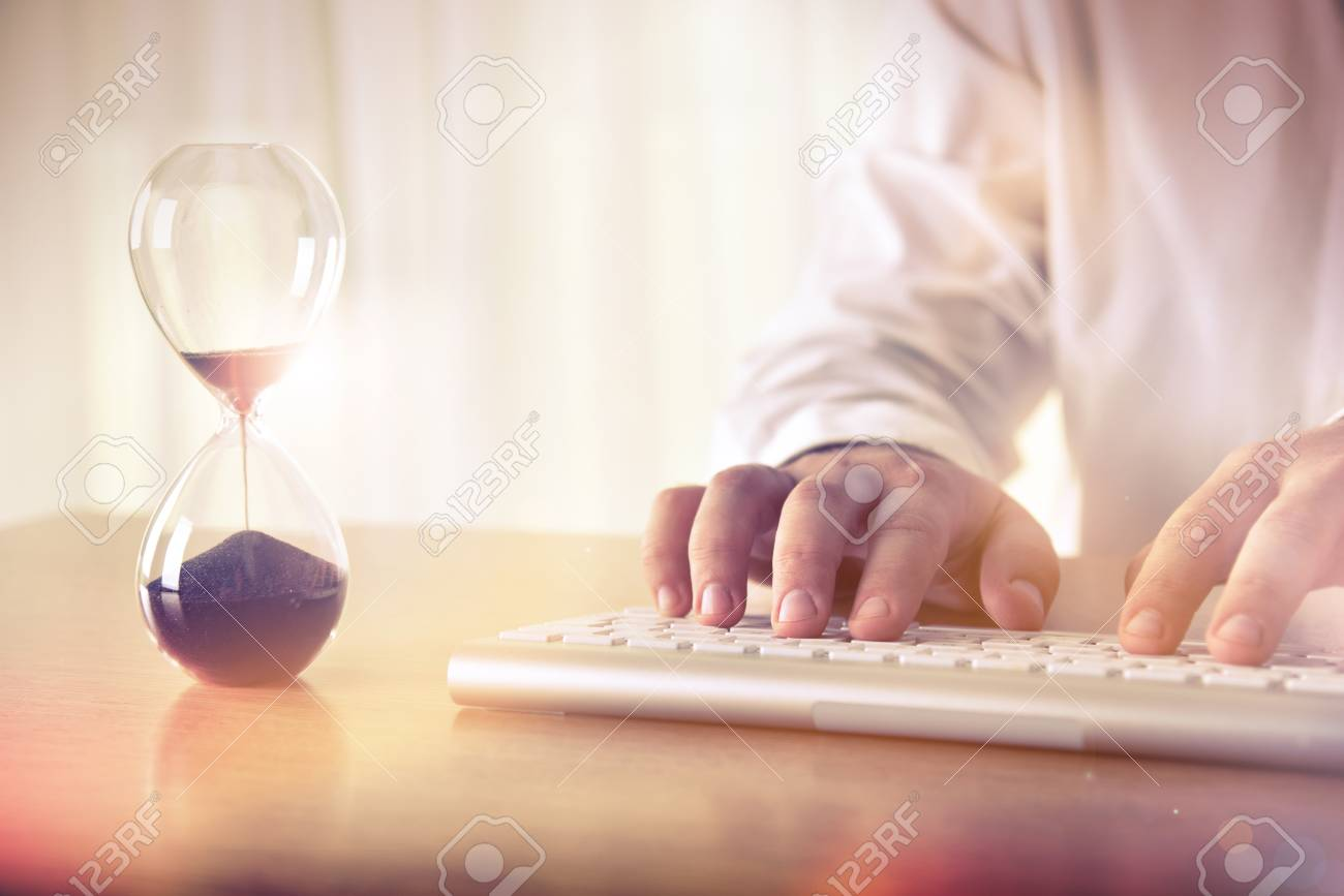 Time management concept. Man's hands typing on computer keyboard next to a hourglass. Concept for background, website banner, promotional materials, presentation templates, advertising. - 79488496