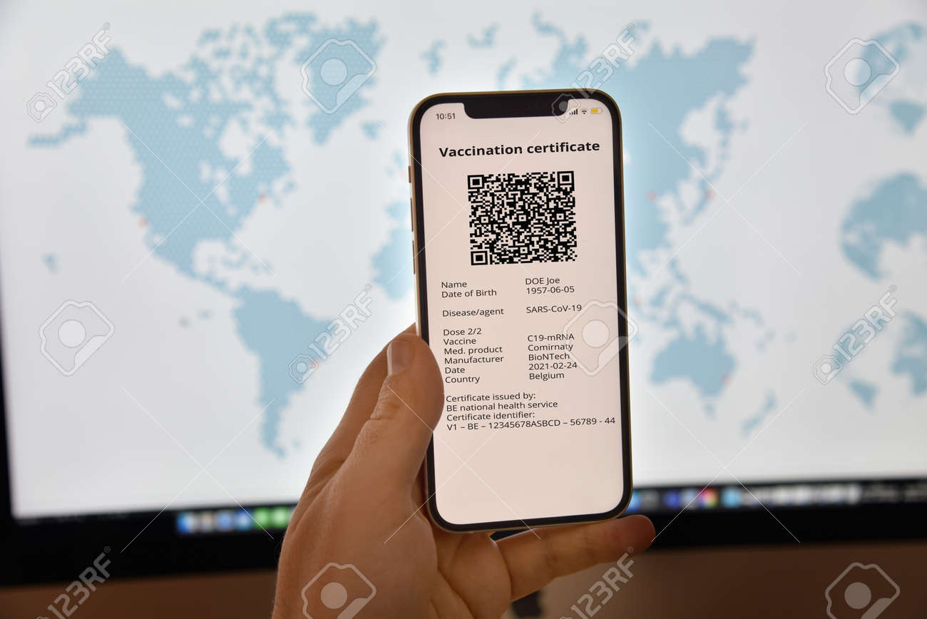 Business and tourism concept of travel during pandemic. A mans hand holds a mobile phone with a digital certificate against in front of the world map. - 167164212